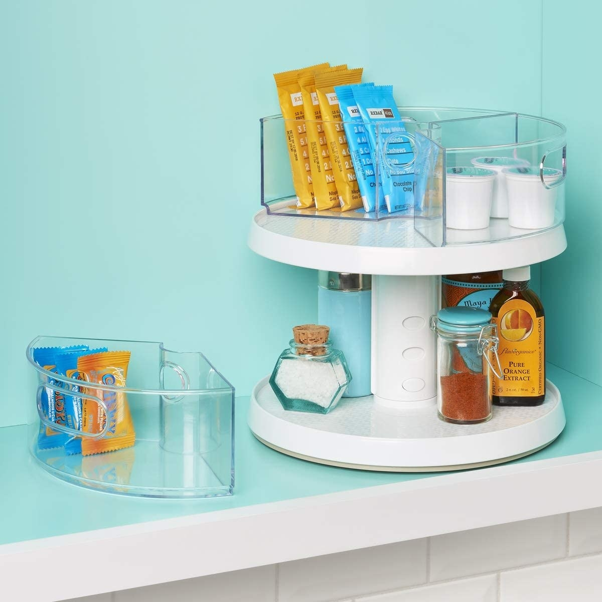 turntable with sugar and honey and other small kitchen items organized neatly on both shelves