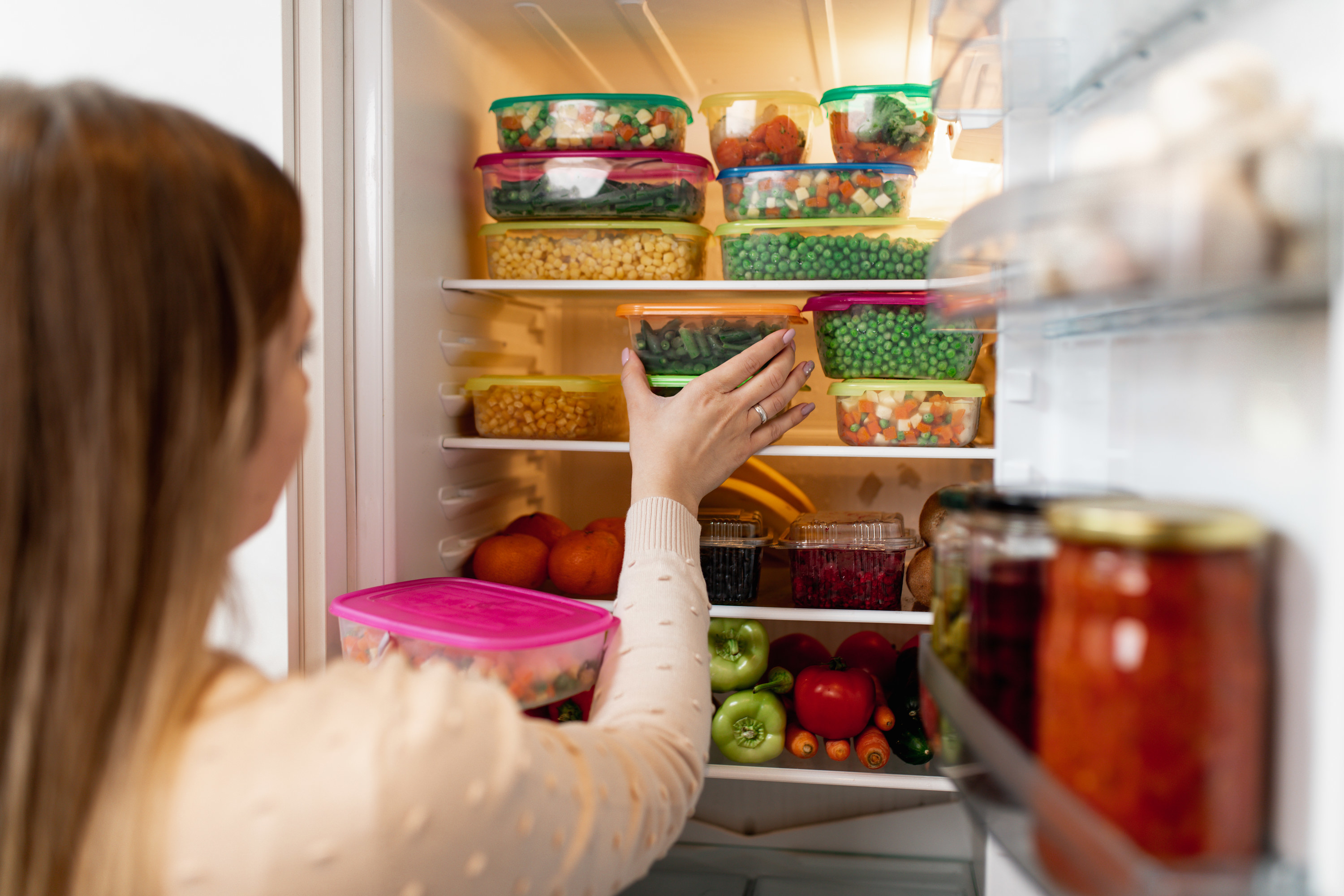Close-up shot of woman putting a food container into the fridge.