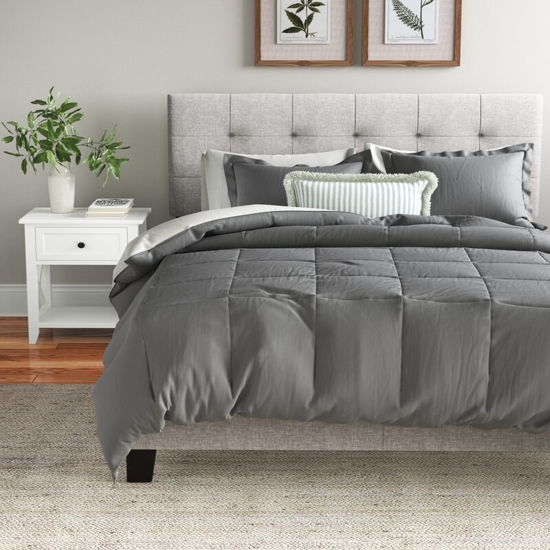 Gray sheets, including a puffy comforter, on a gray bed next to a white side table