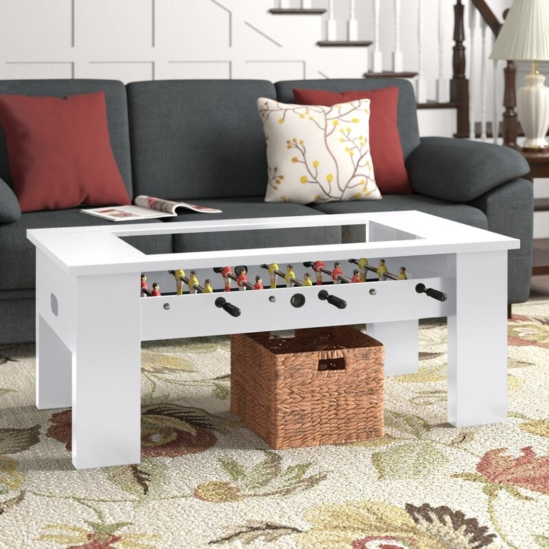 A white foosball table that also is a coffee table in a living room
