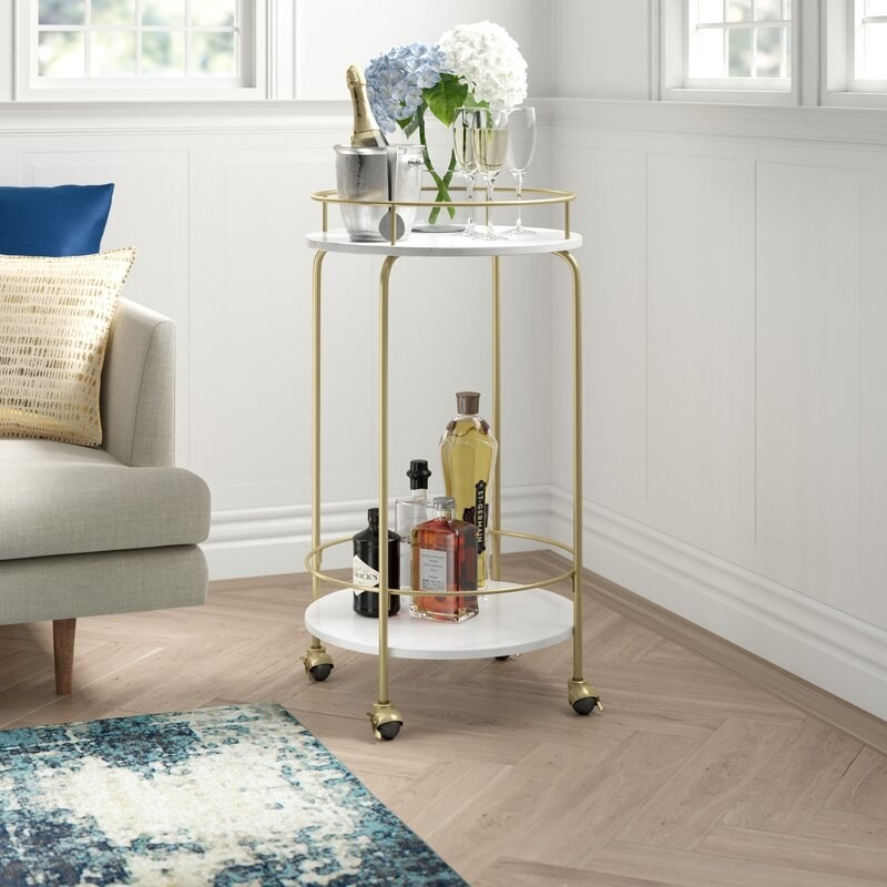A rounded bar cart with liquor, wine glasses, and a champagne bottle in ice in a living room next to a couch