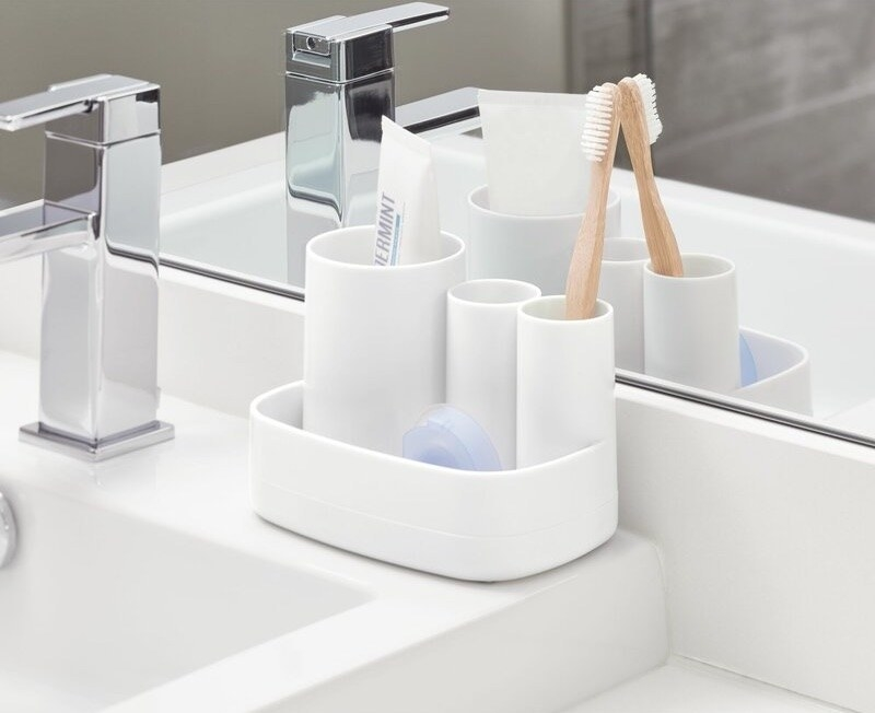 A contemporary white toothbrush holder with toothpaste an da toothbrush in it