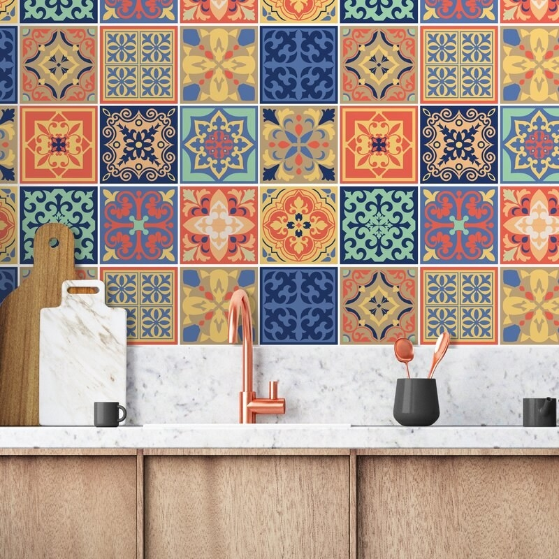 A kitchen with a colorful wall that has fun mosaic tile on it