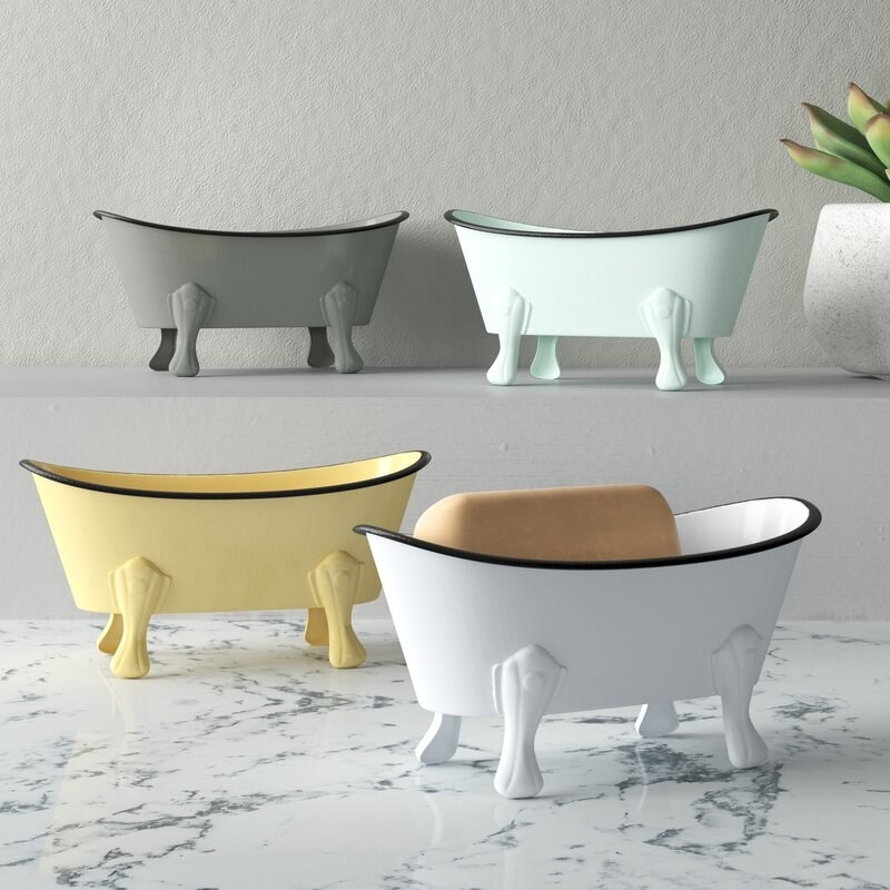 Four soap dishes that look like mini bath tubs in different colors -- gray, teal, yellow and white on a marble counter