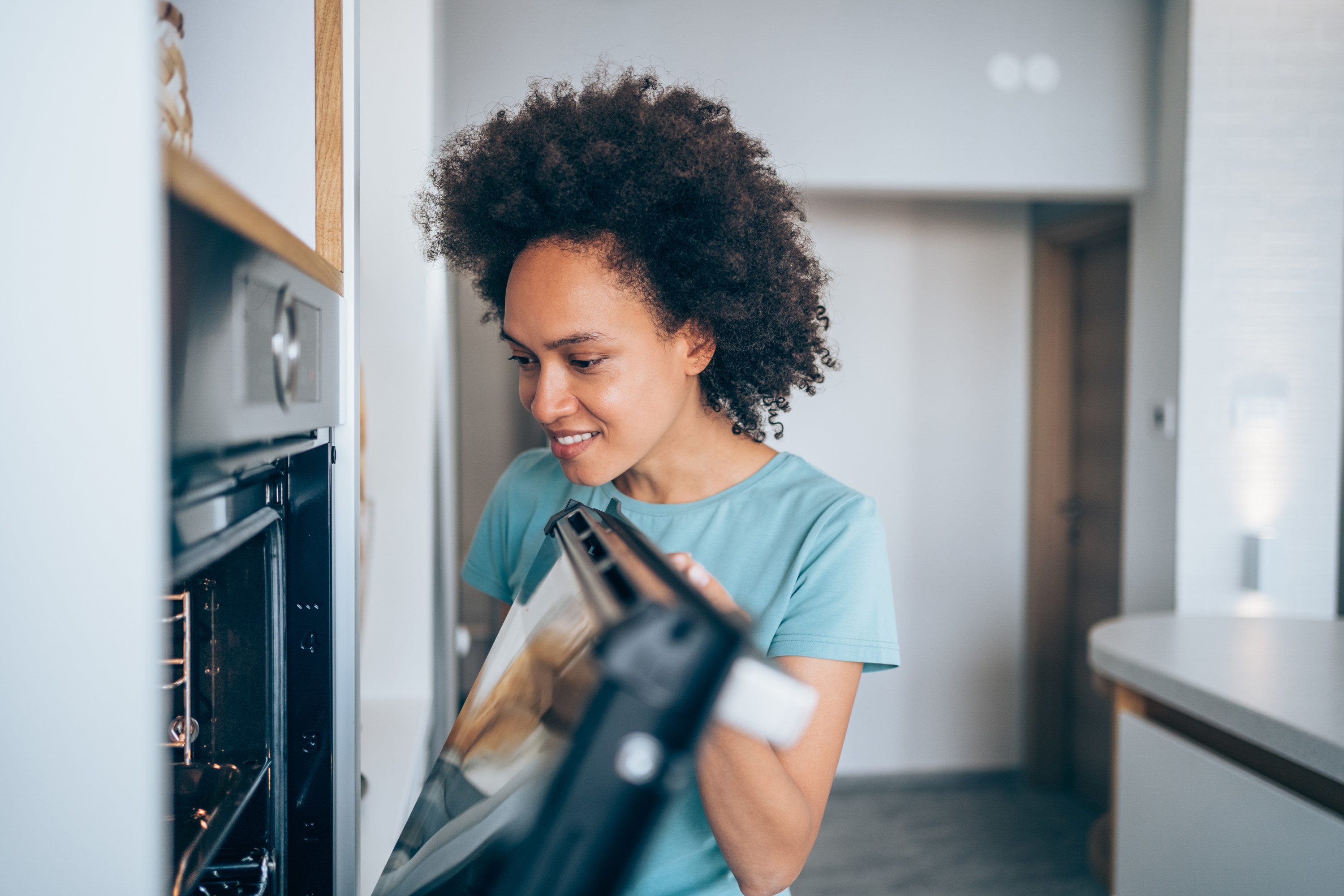 Smiling woman checking food in the oven.