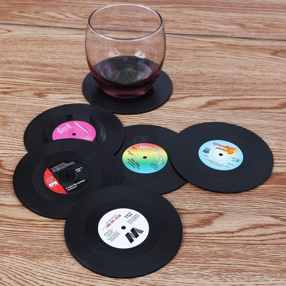 The six coasters laid out on a table, one has a drink on it