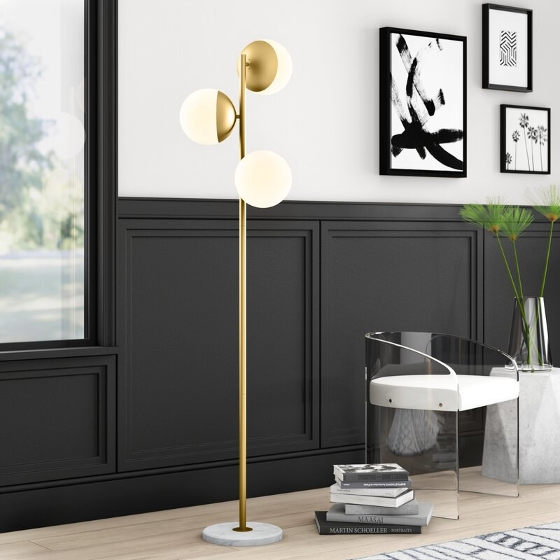 A standing gold lamp with three ball bulbs in a modern living room with black wainscoted walls
