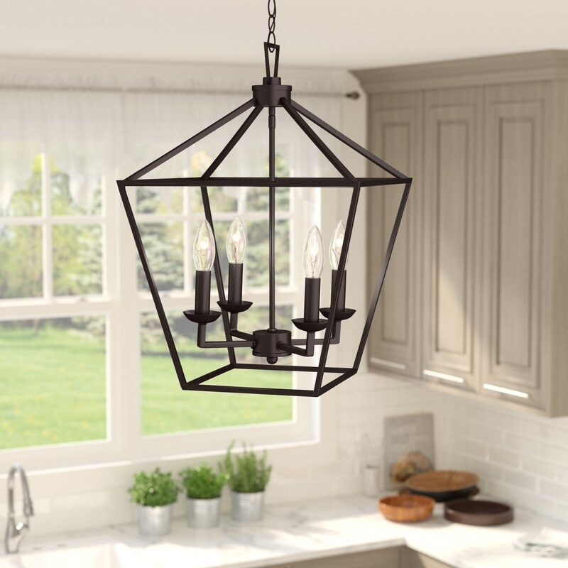 A large lantern-designed pendant light in a kitchen holding four lightbulbs that look like candles