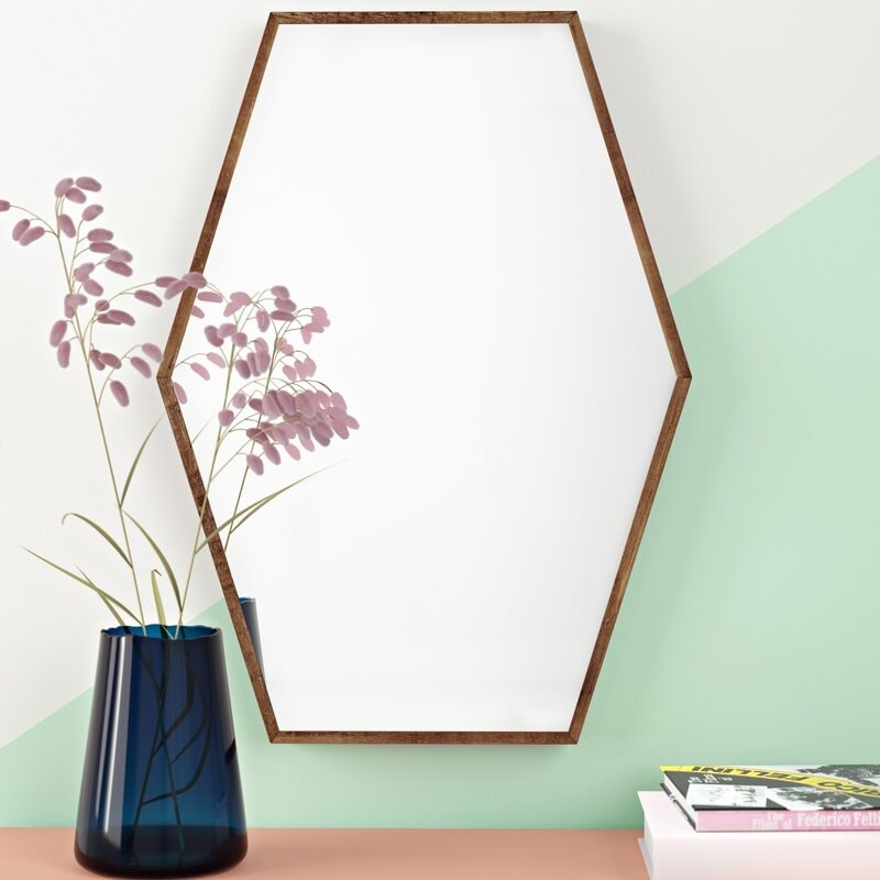 A hexagon-shaped accent mirror next to a vase with flowers and stack of books
