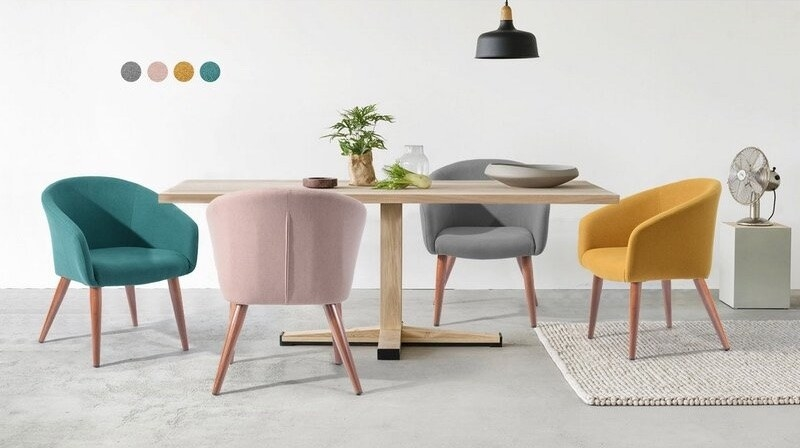 A set of colorful chairs each in a different color surrounding a brown wooden dining table