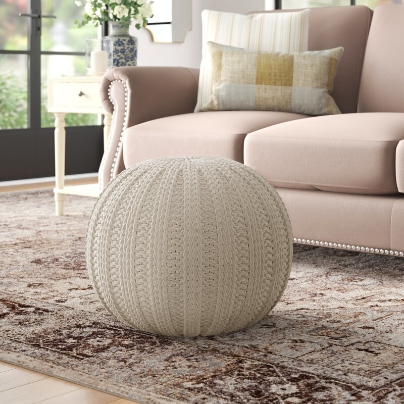 A cream-colored pouf ottoman on a brown oriental rug next to a taupe couch