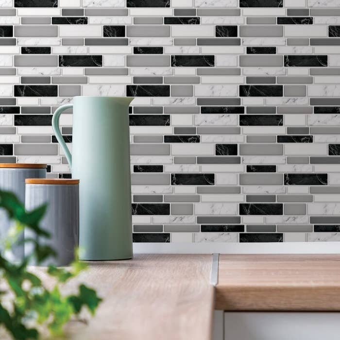 A black, gray and white backsplash tile in a kitchen with a butcher block counter top