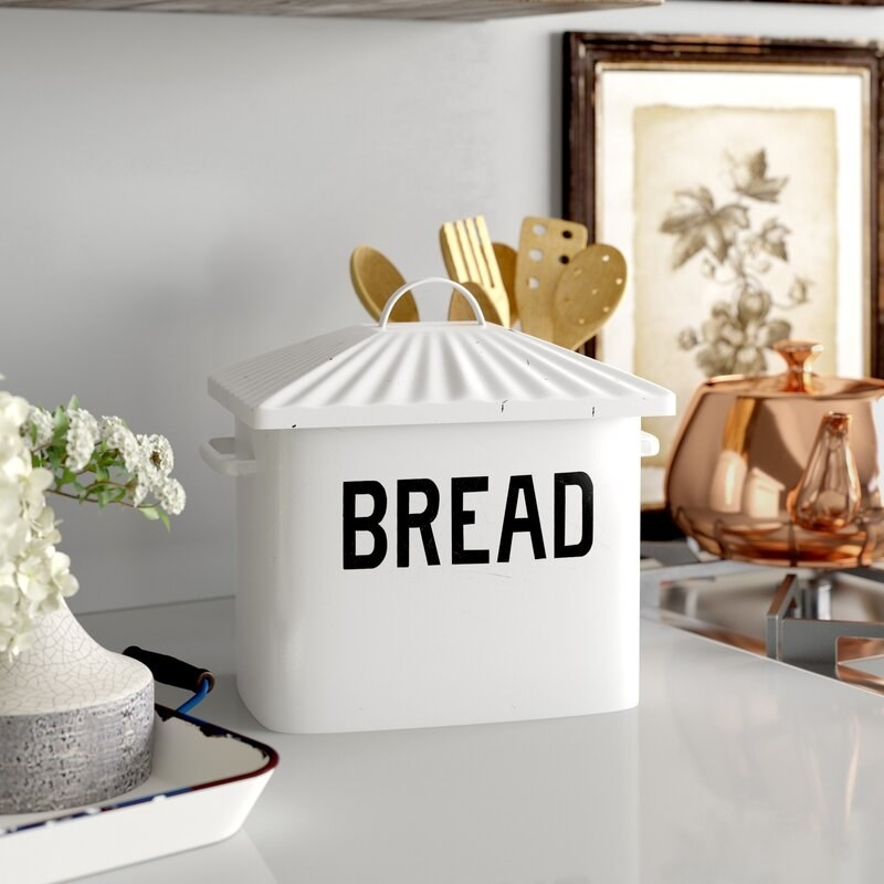 """A white metal bread box with the word """"bread"""" on it written in black typography on a kitchen counter"""