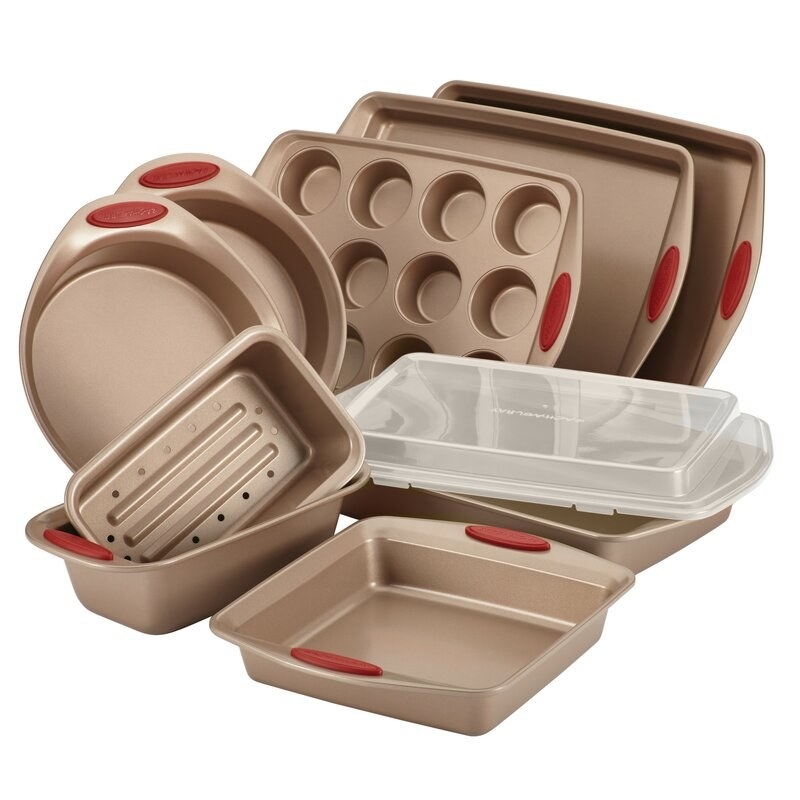 A set of copper-colored baking pans and cookware with red handles