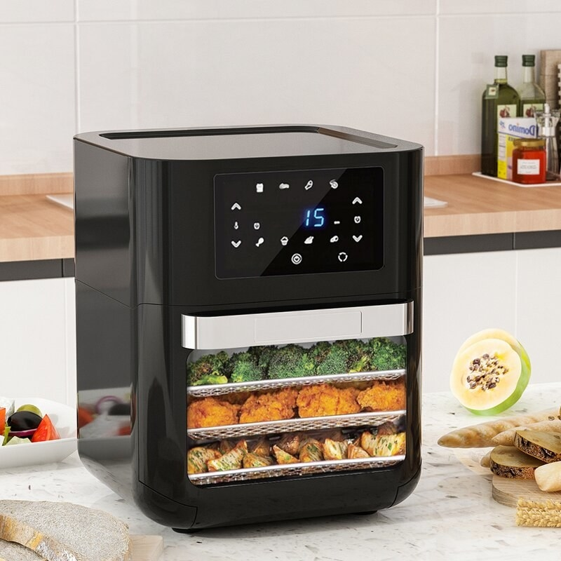 A black air fryer on a kitchen counter with three layers of food inside