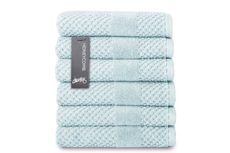 A stack of six blue hand towels folded neatly