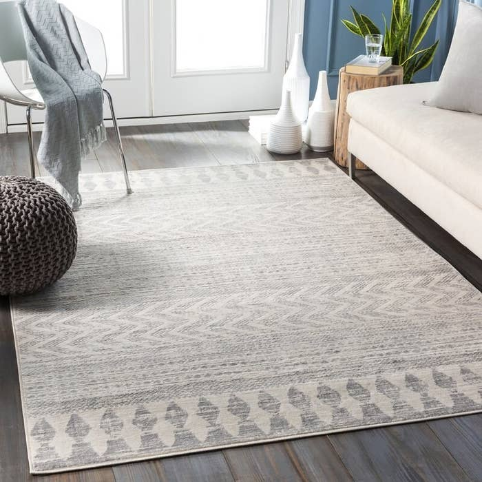 A gray tribal-patterned rug in a living room with a beige couch and gray pouf ottoman