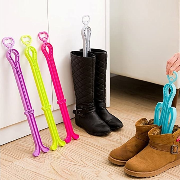 A hand placing one of the boot shaper stands into a pair of ankle boots next to three standalone stands and one stand inserted into a pair of knee-high boots