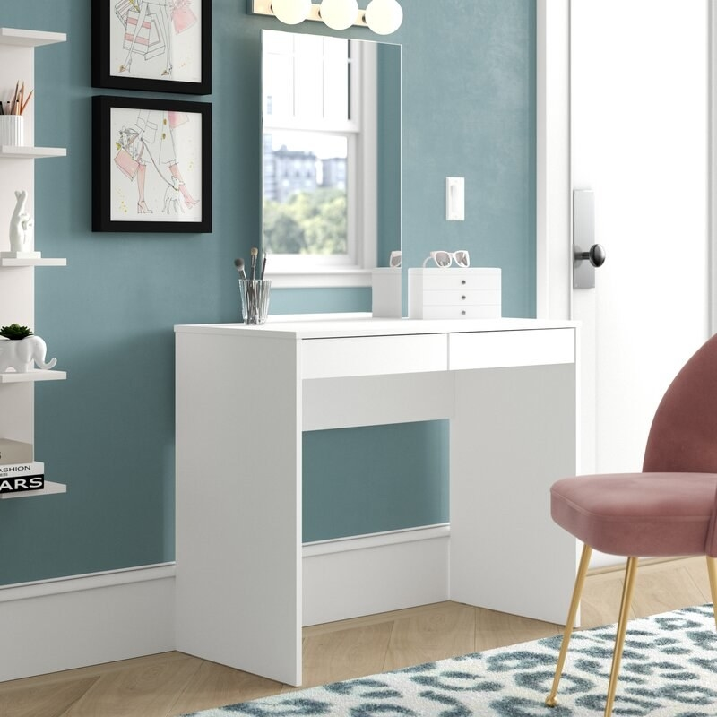 A simple white vanity with a mirror that could also be a desk next to a pink chair in front of a blue wall