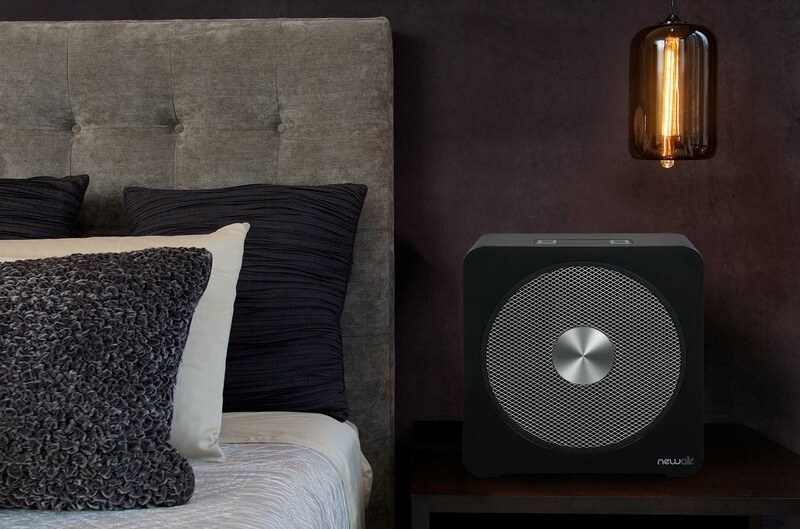 A cozy bedroom with a black heater fan on a bedside table