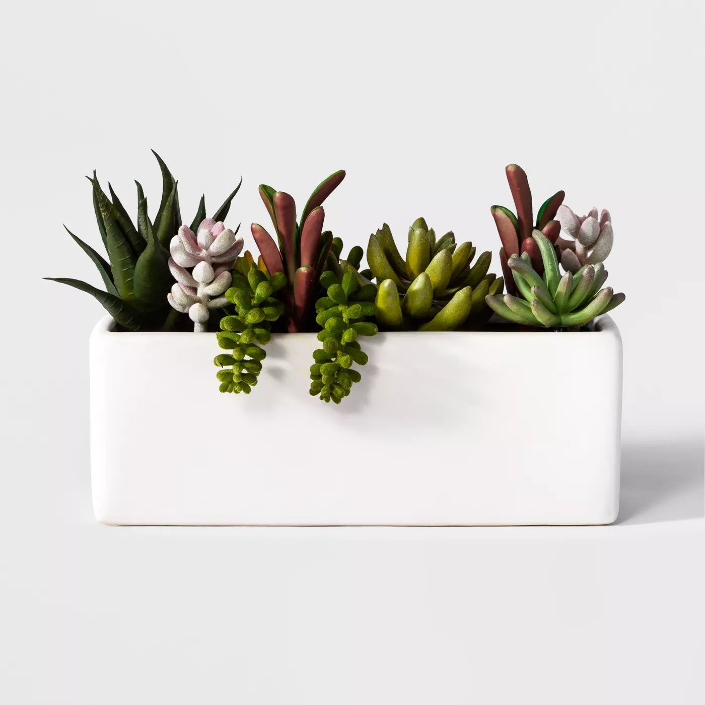The rectangular white planter filled with small faux succulents