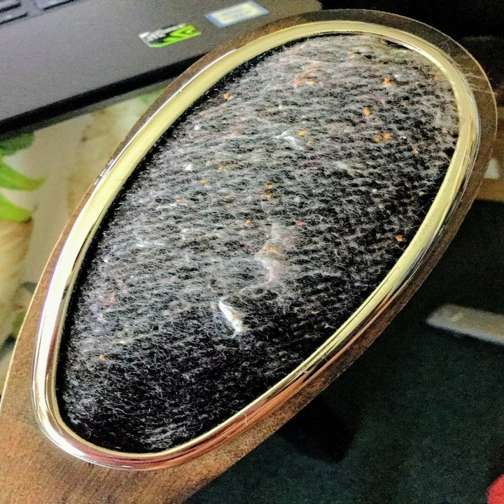 A reviewer photo of the other side of the brush showing a black lint remover with lint all over it