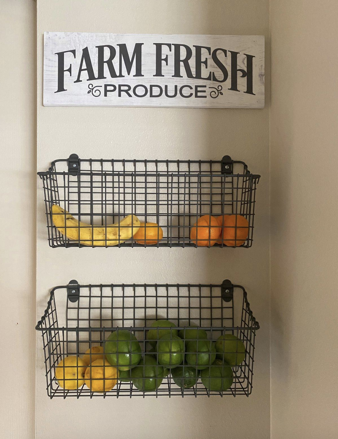"reviewer image of two baskets attached to the wall with limes and lemons and a sign above that says ""farm fresh produce"""