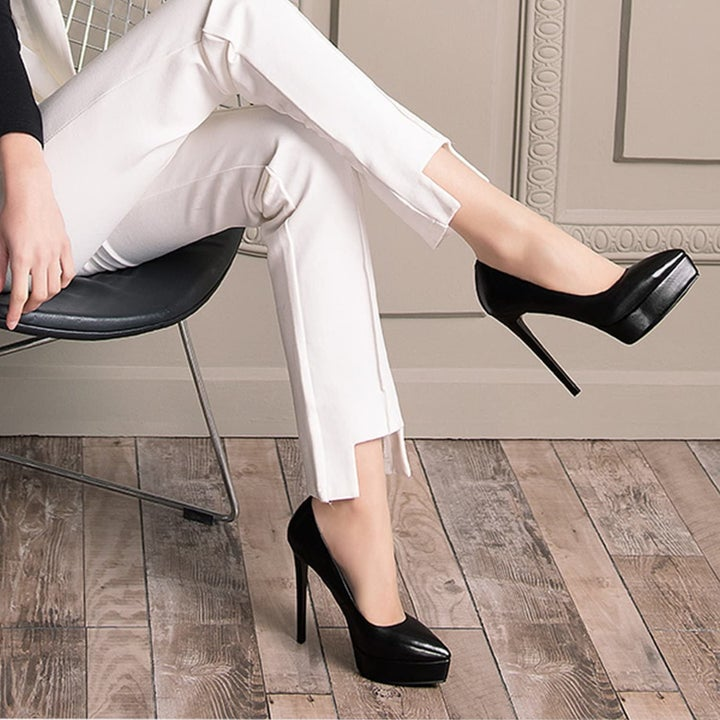 A model wearing a pair of black stilettos with the replacement tips on the heels