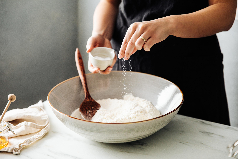 Woman sprinkling salt in flour before mixing