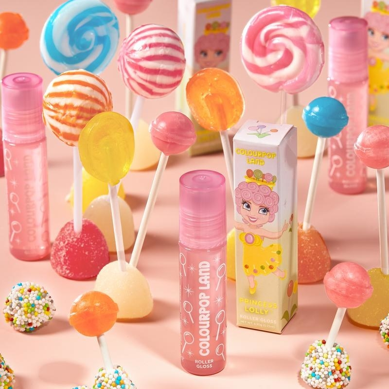 pink glittery lip balm that has white illustrated lollipops on it next to box with lollipop princess on it