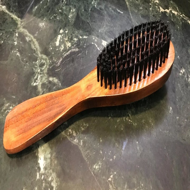 A reviewer photo of a wooden brush with black bristles sitting on a marble countertop