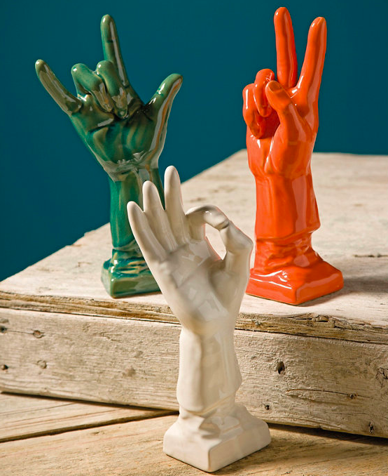 Three ceramic hands in different colors with the slang signs for peace, love, and harmony