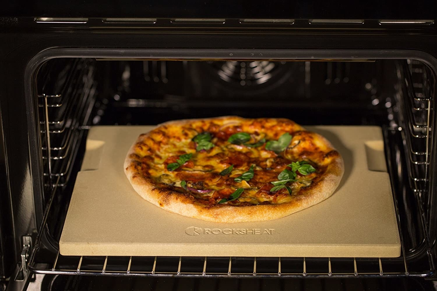 A homemade pizza cooking on the pizza stone in an oven