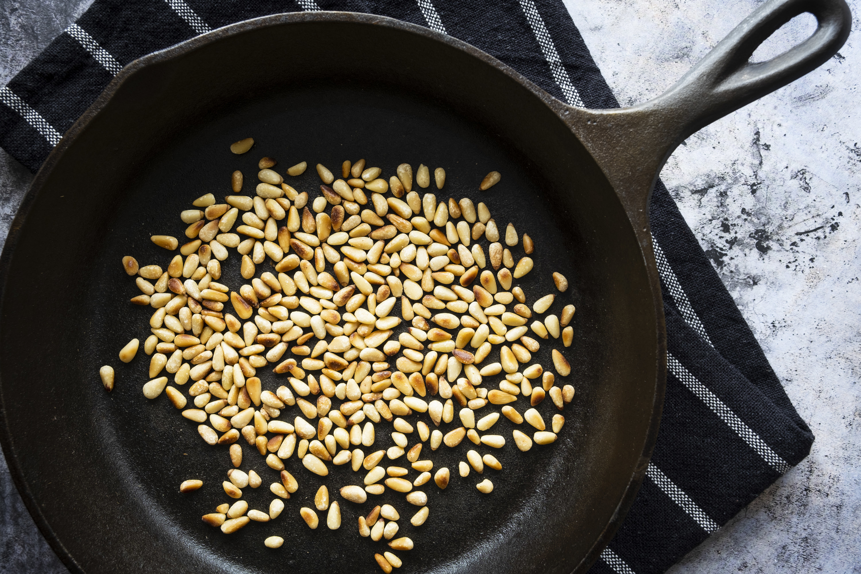 Toasted pine nuts in a cast iron skillet on a black tea towel.