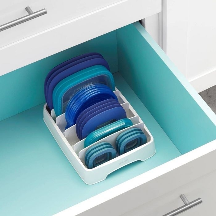 the YouCopia StoraLid container lid organizer in a kitchen drawer