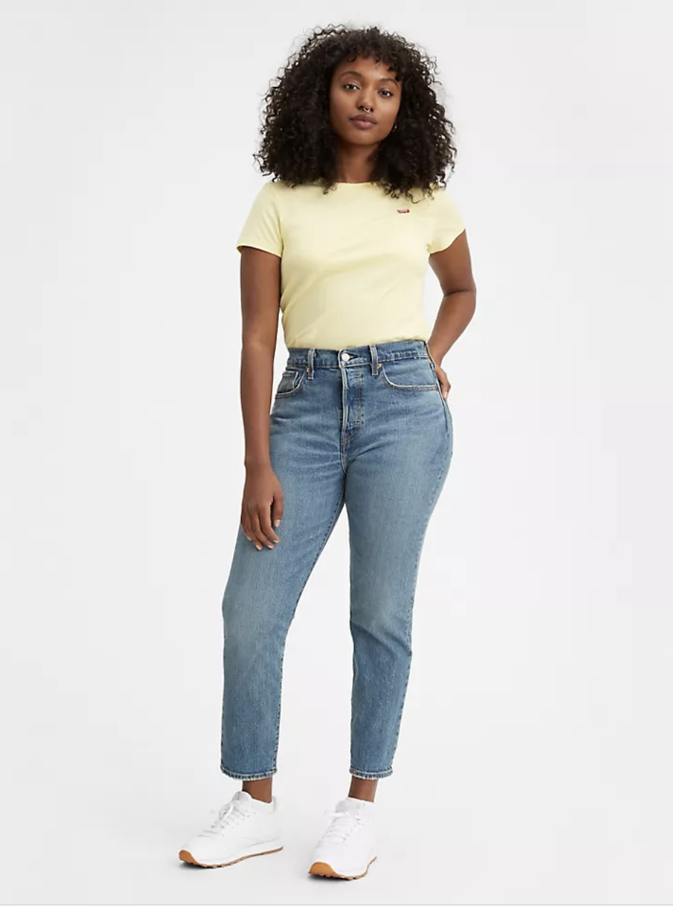 A model in medium wash high waisted denim ankle jeans