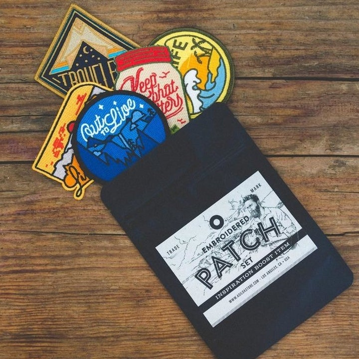 A black packaged with five different-colored embroidered adventure-themed patches spilling out