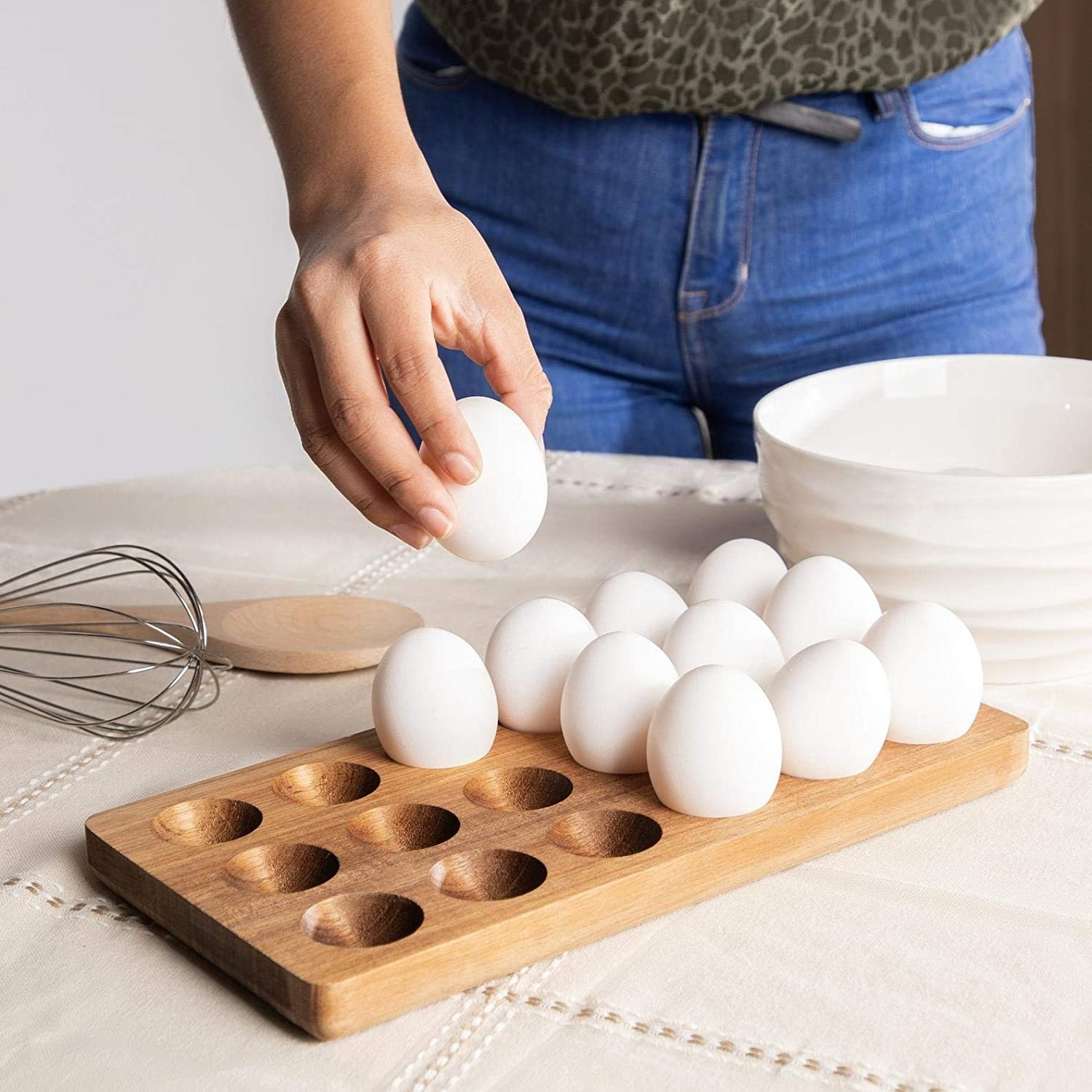 A model grabbing an egg from the wooden holder which can hold 18 eggs