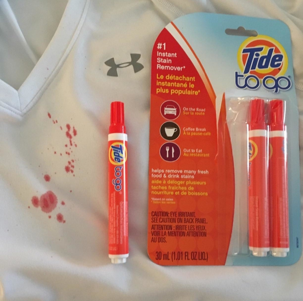 A reviewer photo of a white shirt with a red stain with three Tide stain remover sticks sitting on top