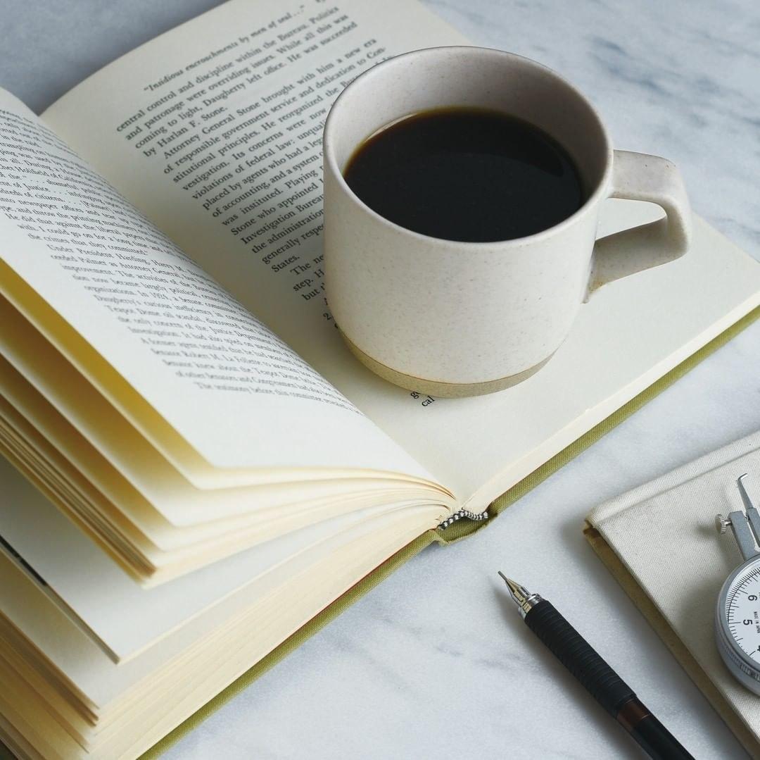 the cream colored mug with coffee inside