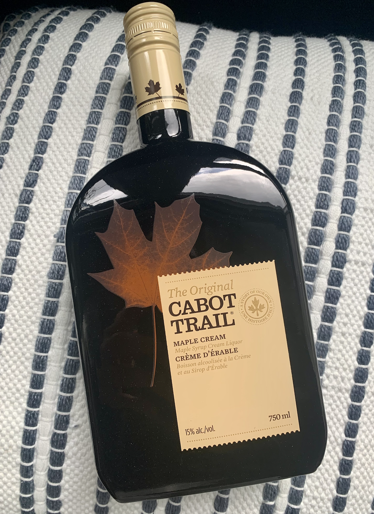 A bottle of Cabot Trail Maple Cream against a blue and white fabric.