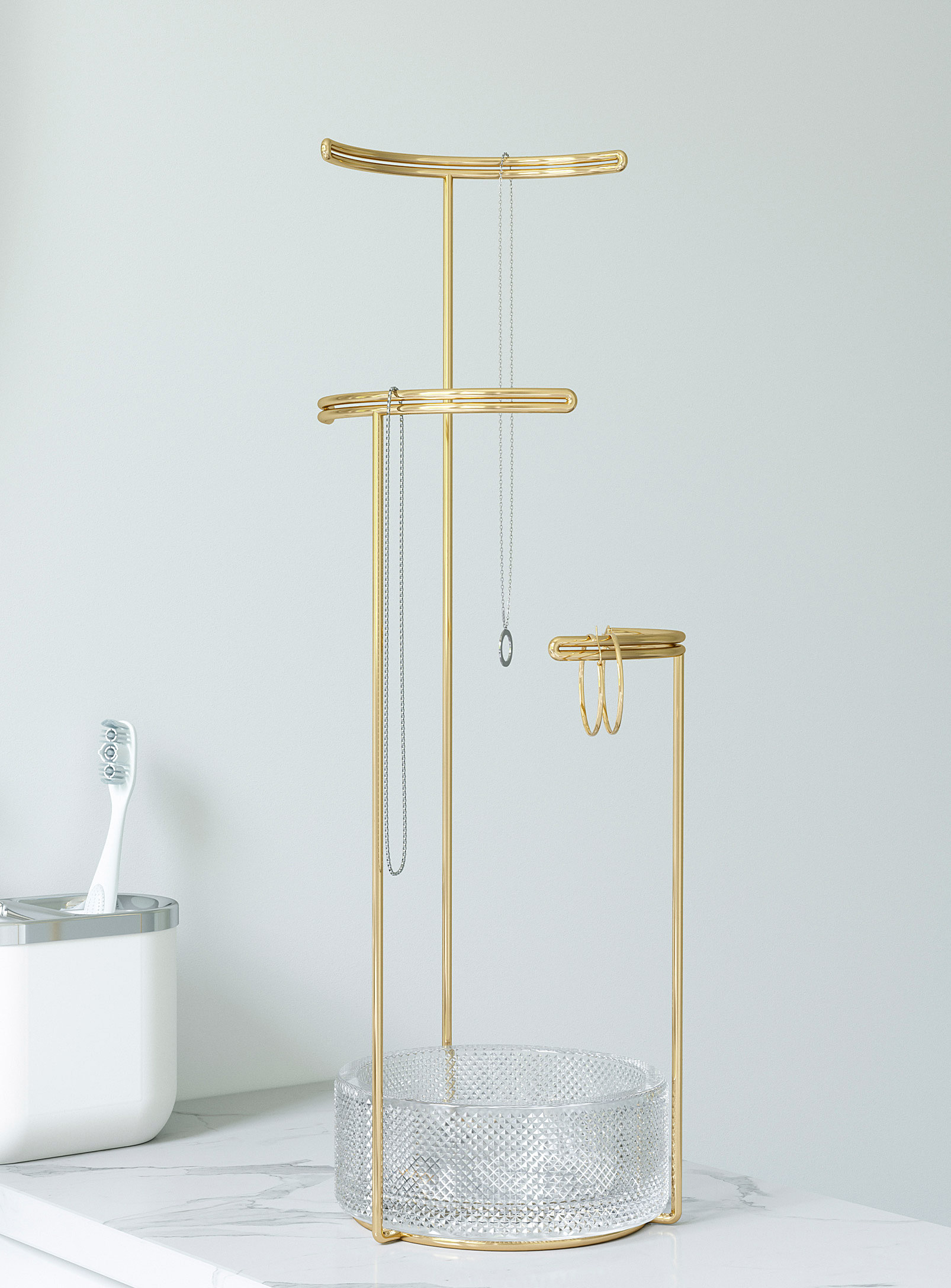 A jewelry stand with three T-shaped bars and a glass bowl at the base