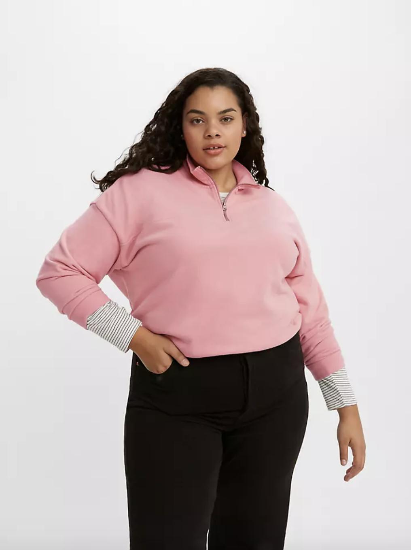 Model in pastel pink quarter zip sweater