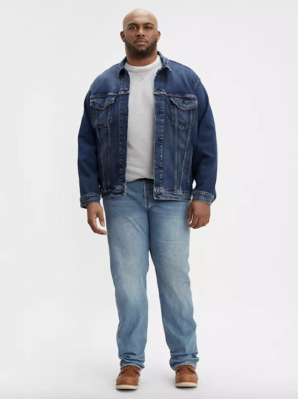 Model in a dark wash denim trucker jacket