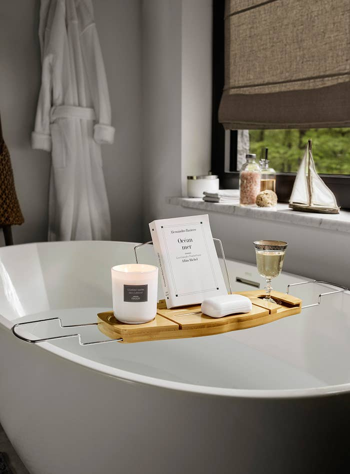 A wooden tray resting across a bathtub A book and a glass of wine are placed on top