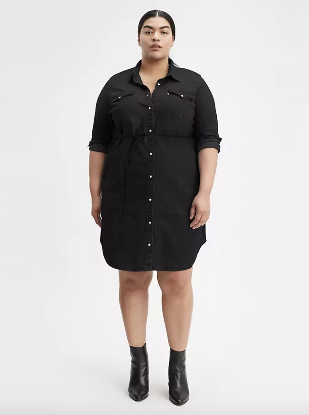 Model in a black button up collared long sleeved shirt dress that cinches at the waist