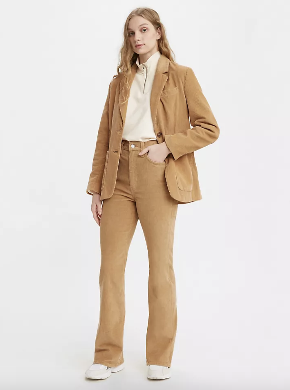 A model in khaki colored boot cut high waisted pants
