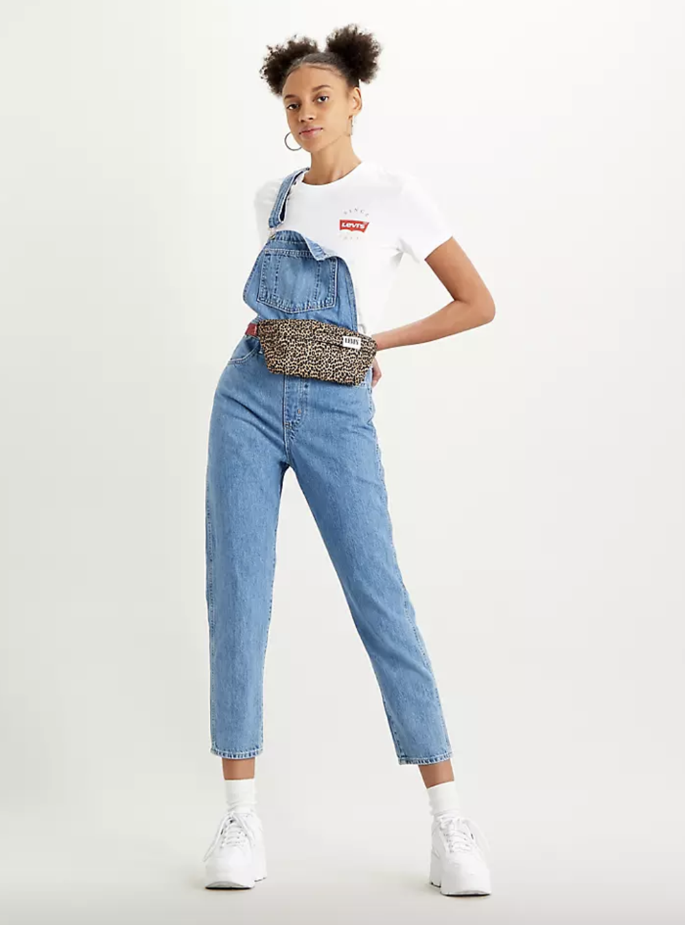 Model in a pair of lightwash overalls that fall at the ankle