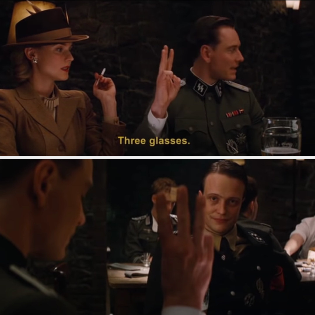 """Hicox says """"three glasses"""" and puts up three fingers (but not his thumb) —as Dieter looks at him suspiciously"""
