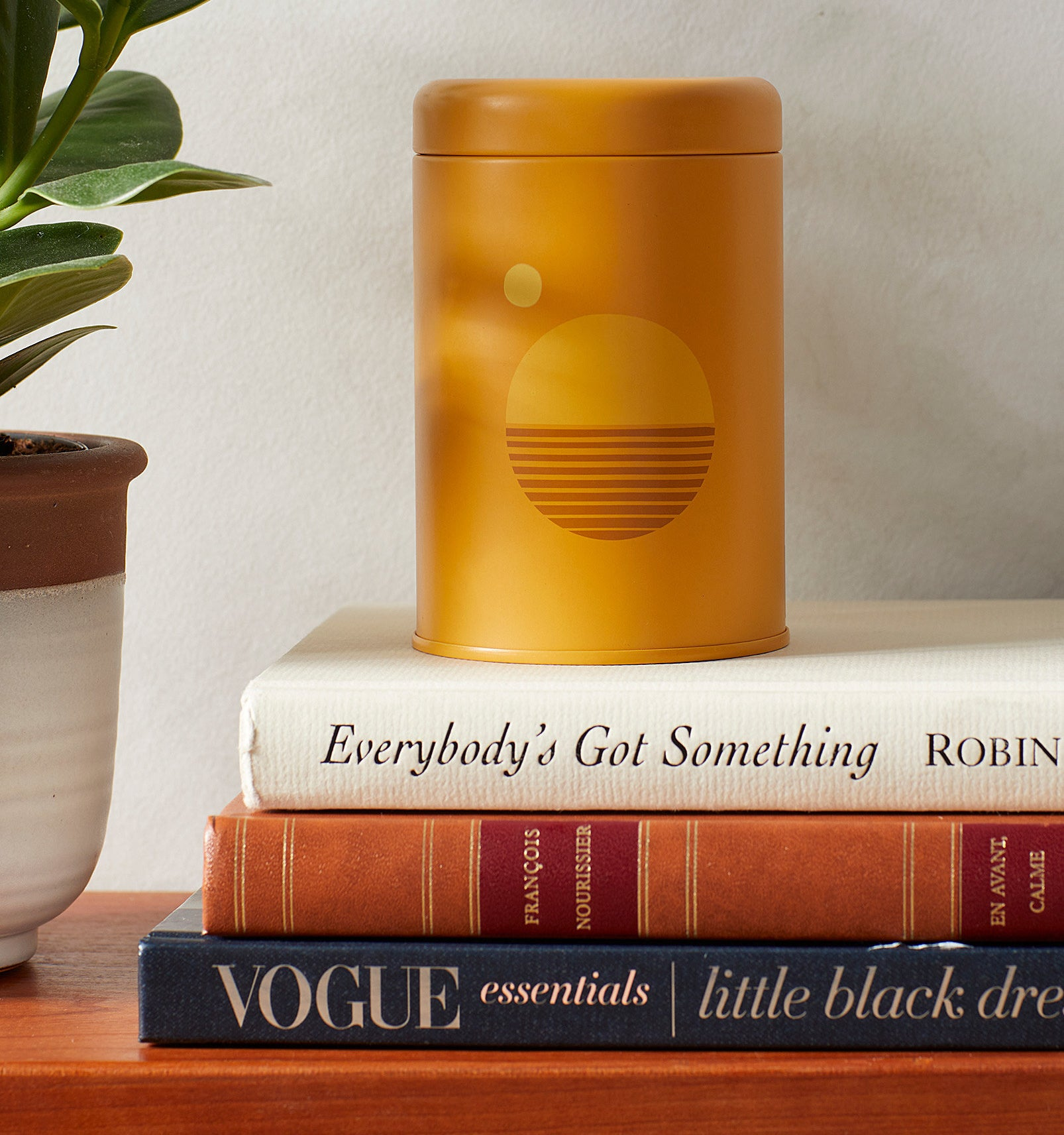 A candle in a small tin jar on a stack of books